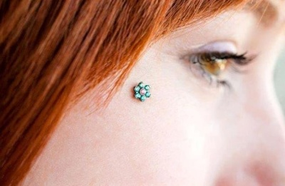 Piercing anti-arcade avec un microdermal couleur turquoise