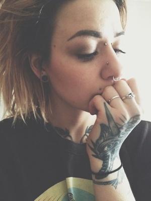 Piercing bridge et tatouage sur la main