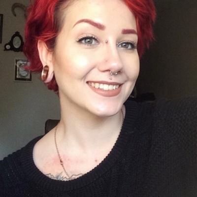 Piercing bridge, tunnel et septum sur femme aux cheveux rouges