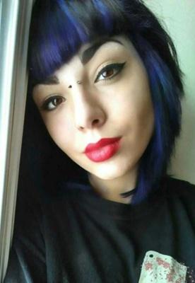 Piercing bridge sur femme avec des cheveux bruns et bleus