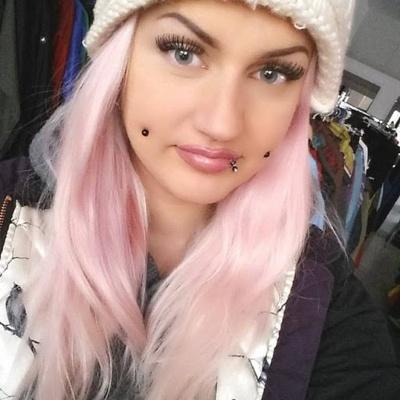 Piercing cheek, joue, fossette plaqué titane noir sur femme aux cheveux roses