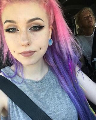 Piercing cheek, joue, fossette sur femme aux cheveux roses et lilas