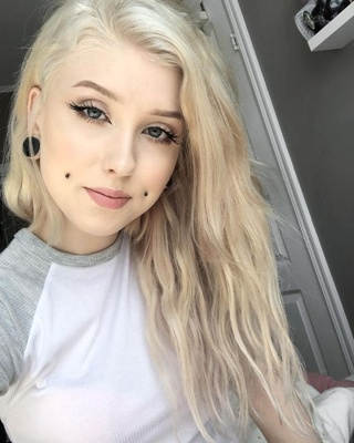 Piercing cheek, joue, fossette sur femme blonde avec un plug au lobe de l'oreille