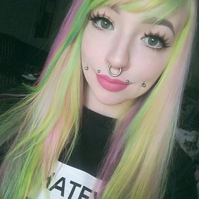 Piercing cheek, joue, fossette sur femme aux cheveux multicolores