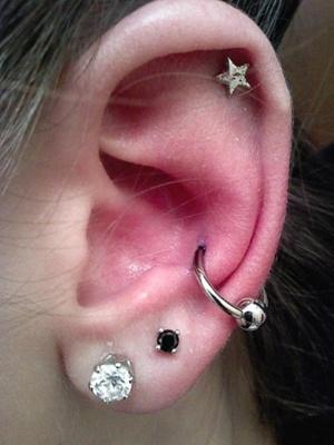 Piercing conch / conque avec un anneau classique argenté et un piercing hélix en forme d'étoile
