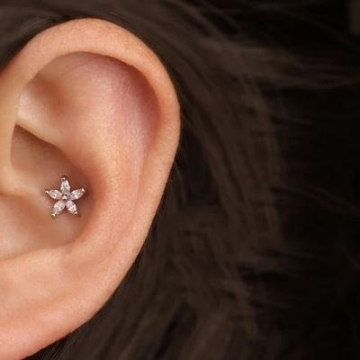 Piercing conch / conque avec une barbell qui représente une petite fleur