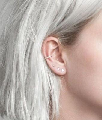 Piercing conch / conque avec un anneau et des piercings triangulaires au lobe de l'oreille