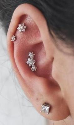Piercing conch / conque qui représente trois fleurs et deux autres fleurs sur des piercings de l'hélix
