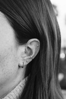 Piercing conch / conque avec un petit anneau fin et un piercing hélix