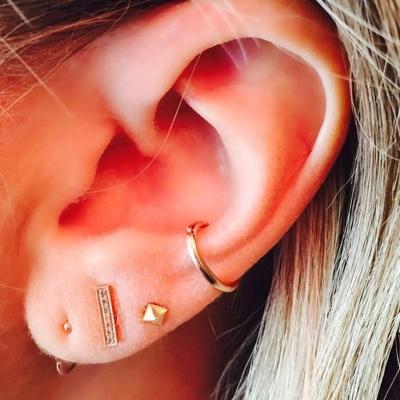 conch / conque avec un anneau jaune et divers piercings du lobe