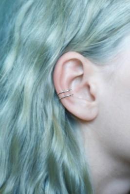 Double piercing conch / conque sur une femme aux cheveux turquoise