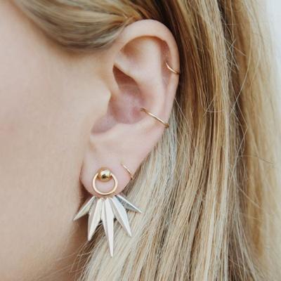 Piercing conch / conque avec un anneau jaune, un piercing hélix et piercings du lobe