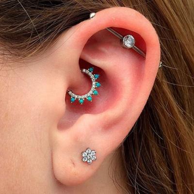 Piercing daith avec un bel anneau aux gems turquoises et un piercing industriel