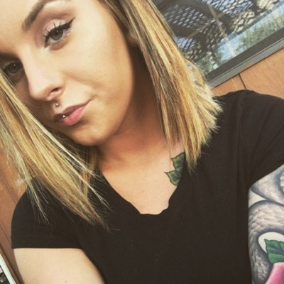 Piercing jestrum sur une fille avec un tatouage au bras