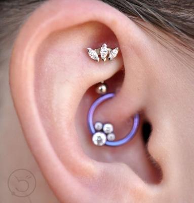 Piercing rook avec une barbell ornée de trois cristaux transparents et un anneau bleu pour un piercing daith