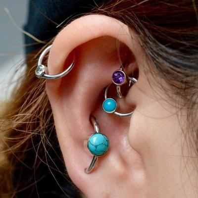 Piercing rook avec un anneau violet et divers autres anneaux
