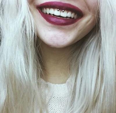 Piercing smiley / frein labial avec un fer à cheval sur femmes aux cheveux blonds clairs
