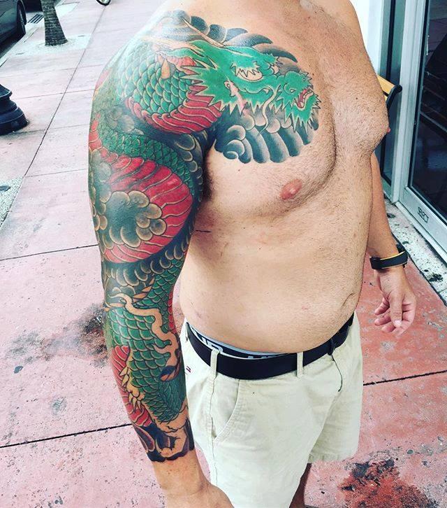 Tatouage dragon coloré du bras réalisé par Ami James