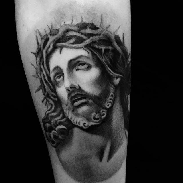 Tatouage Jésus en noir et gris réalisé par Ami James