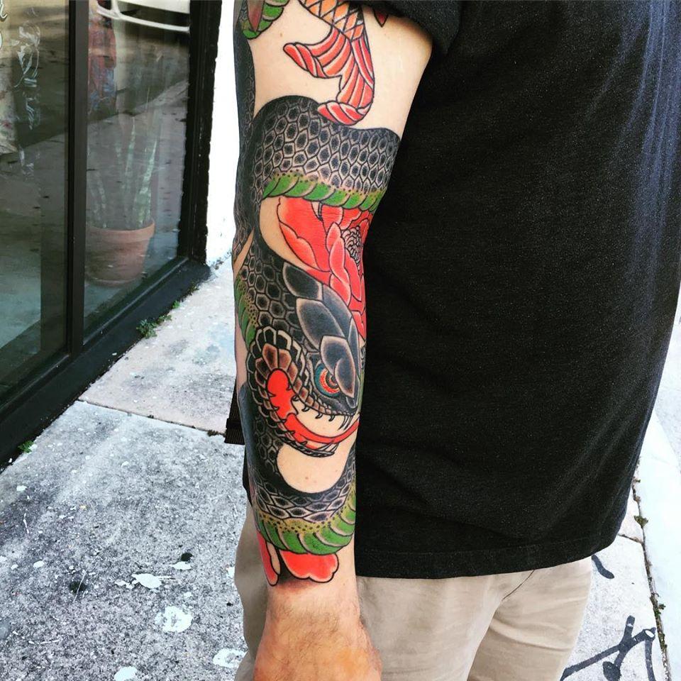 Tatouage dragon coloré sur le bras réalisé par Ami James