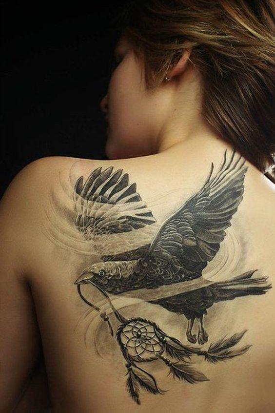 Tatouage d'un corbeau tenant un attrape rêve