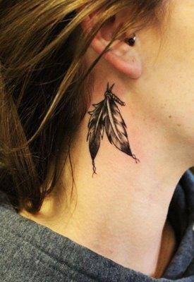 Tatouage de deux plumes sous l'oreille