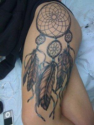 Tatouage plume attrape rêve avec trois plumes sur la cuisse