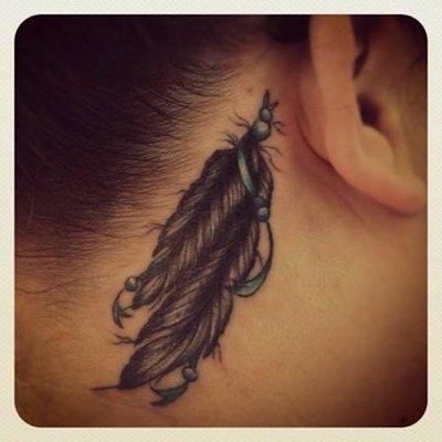 Tatouage de deux plumes derrière l'oreille