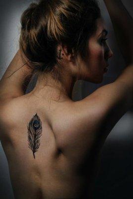 Tatouage plume au milieu du dos