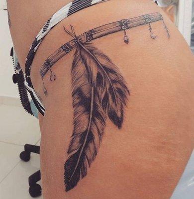 Tatouage de deux plumes sur la hanche